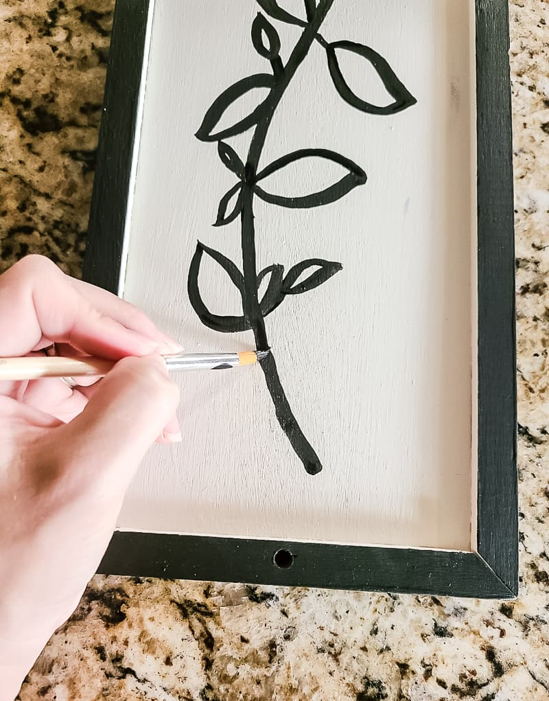 Painting the flower stem outline with black acrylic paint using a paint brush