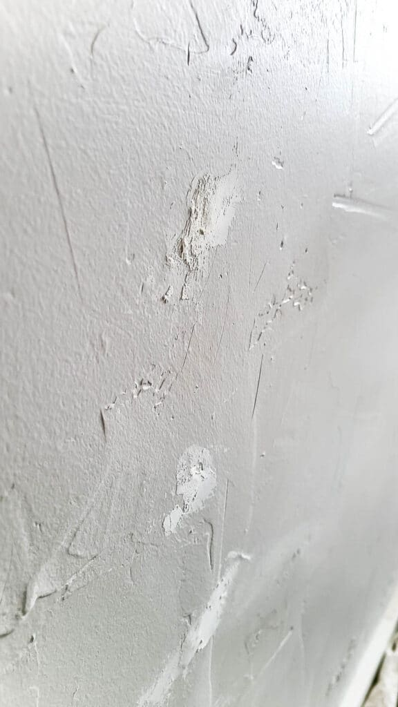 Side view of the white wall with spackle covering the nail hole