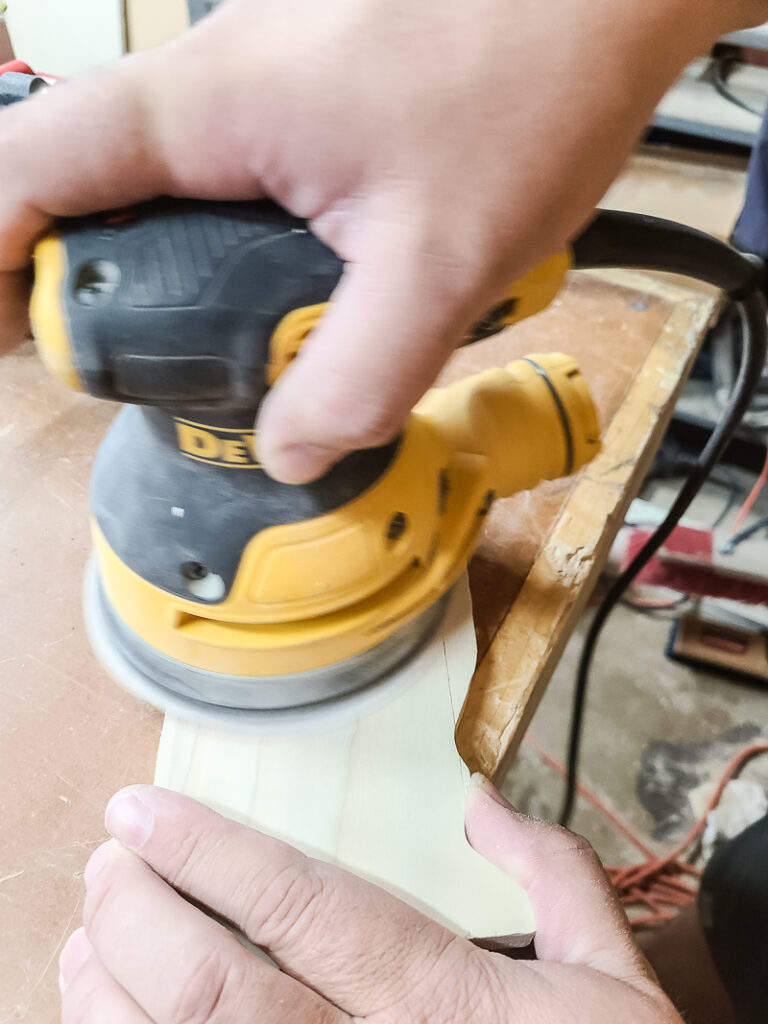 Man sanding the cut out wood coaster with orbital sander