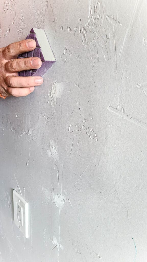 Sanding the spackle on the white wall with sand block