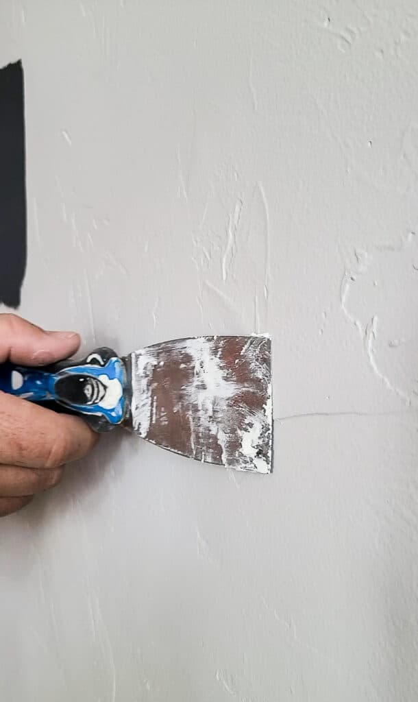 Flattening the spackle using a putty knife