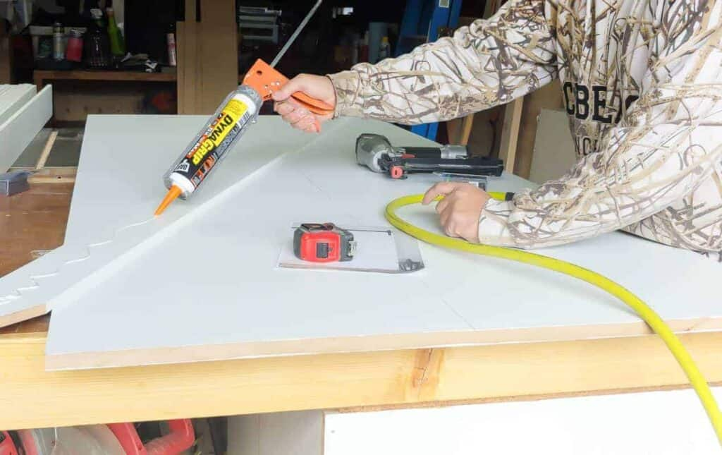 Putting glue at the back of a cut MDF wood on the working table