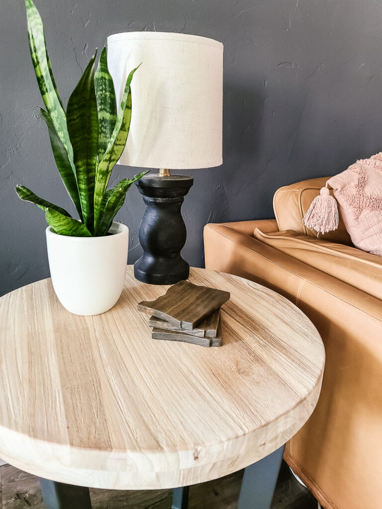 Three pile of diy wood coasters with state shape on the wooden side table with the lamp and indoor plant