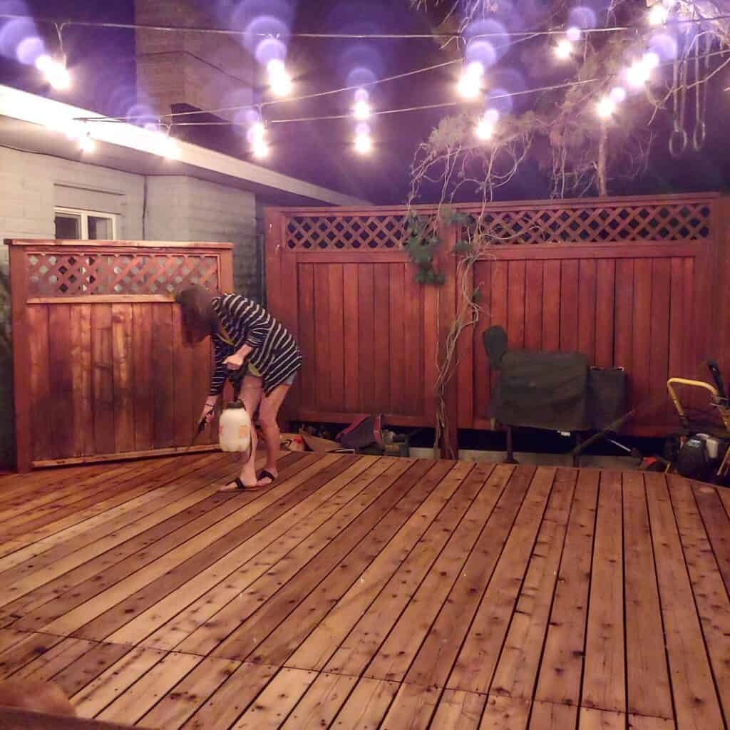 Woman spraying water to clean the deck